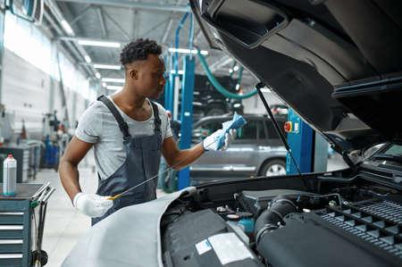 Male mechanic checks oil level, car service Standard-Bild