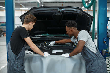 Two male mechanics checking motor, car service