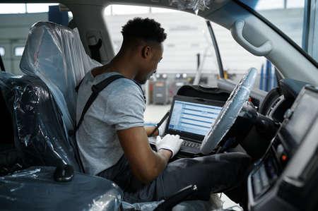Male mechanic using laptop, car service Zdjęcie Seryjne