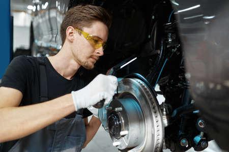 Male mechanic checks brake disk, car service