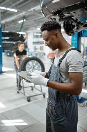 Mechanic using laptop, car on lift, auto service