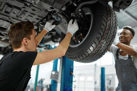 Two male workers fixes wheel, car service Zdjęcie Seryjne