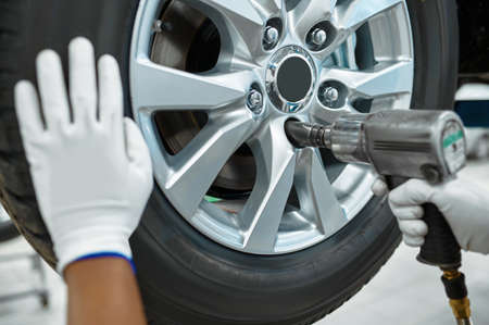 Male mechanic fixes wheel, car service