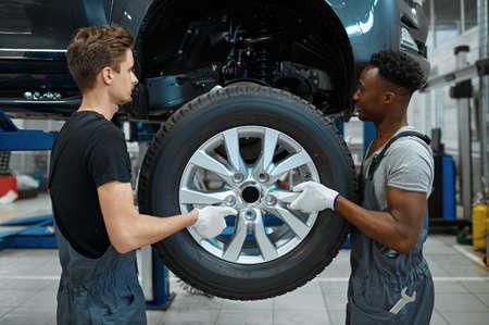 Two male mechanics fixes wheel, car service