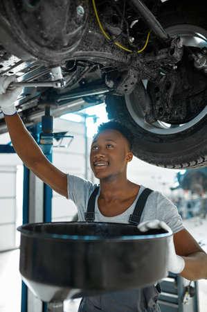 Male mechanic drains the oil, car service Zdjęcie Seryjne