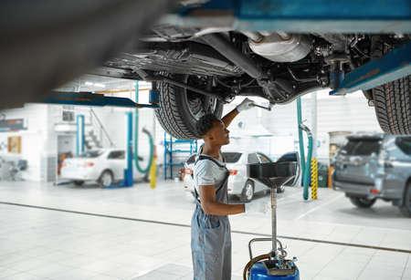 Male mechanic drains the oil, car service Zdjęcie Seryjne - 168383344