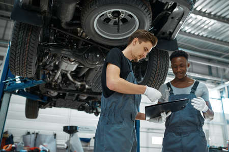 Male mechanics looking on checklist, car service