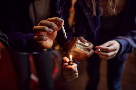 Drug addict man and woman smokes in hellhole