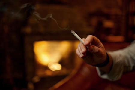 Male hand holds cigarette, fireplace on background