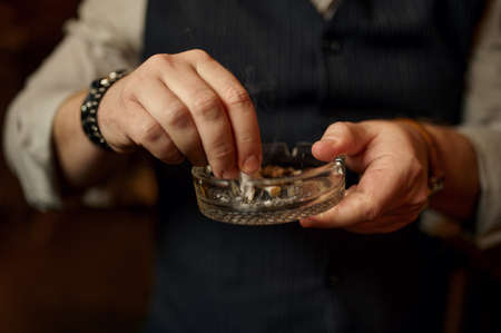 Man puts out a cigarette in ashtray, closeup view