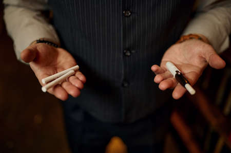 Man holds cigarettes and mouthpiece in his hands