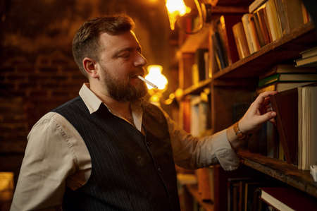Bearded man with cigarette takes book, smoke habit Imagens