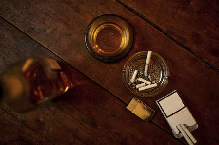 Cigarettes in ashtray, alcohol in bottle, top view Imagens