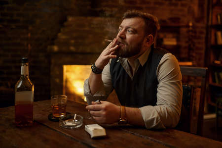 Man smokes cigarette and drinks alcohol beverage