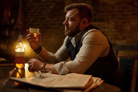 Businessman smokes cigarette and drinks alcohol