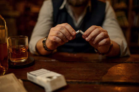 Man breaks a cigarette, bad habit and addiction Imagens
