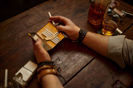 Serious man holds cigarette case Imagens