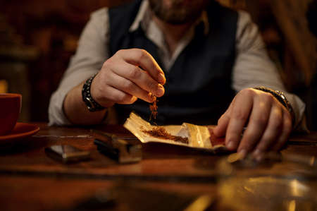 Man grinds tobacco, wooden table on background