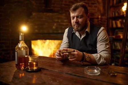 Man with guillotine cuts a cigar, tobacco smoking Imagens