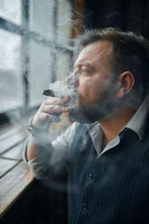 Man at the windowsill and smokes a cigar Imagens