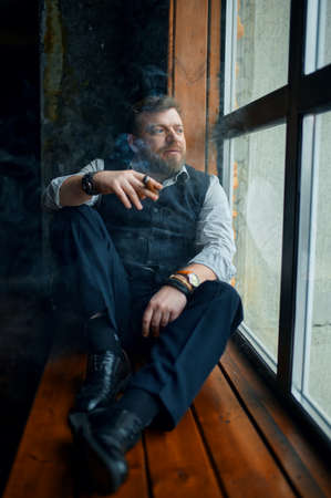 Man sitting on the windowsill and smokes a cigar