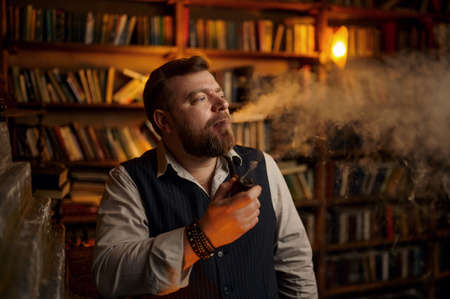 Serious bearded man smokes a cigar in office
