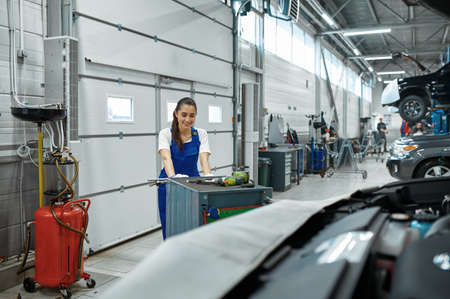 Female mechanic stands at the hood, car service Imagens