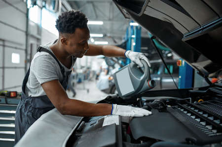 Male worker changes oil in engine, car service Imagens