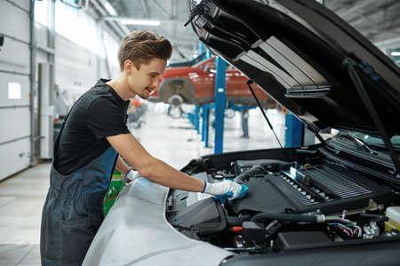 Male mechanic closes the hood, car service Imagens