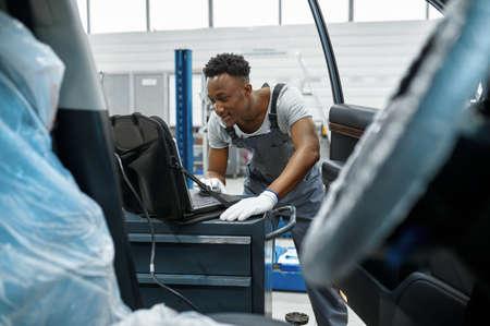 Male mechanic using laptop, car service Imagens