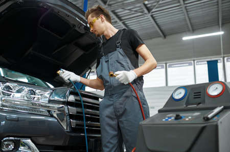Male mechanic refills air conditioner, car service