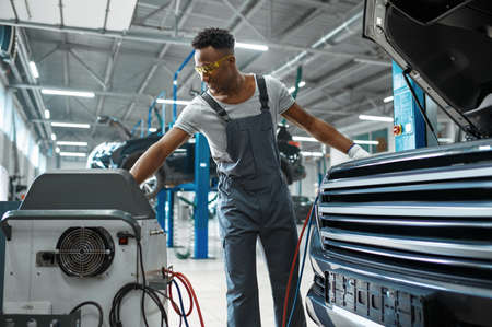 Male worker refills air conditioner, car service Imagens