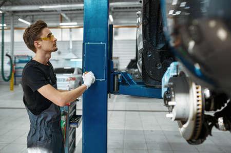 Male mechanic lifts the car, auto service