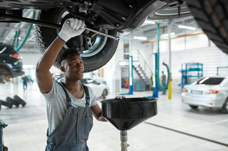 Male mechanic drains the oil, car service Imagens
