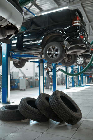 Car wheel and auto on lift, tire service concept Imagens