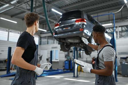 Two male mechanics talking in car service