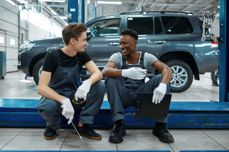 Two mechanics sitting on car lift in auto service Imagens