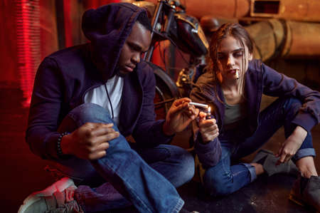 Drug addict man and woman smokes a cigarette