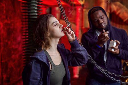 Drug addict man and woman smokes in shebang Imagens