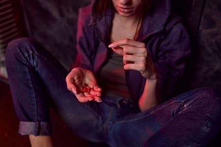 Drug addict female person holds pills, den Imagens