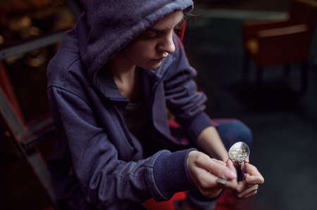 Drug addict with spoon and fire prepares dose Imagens