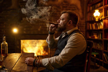 Man smokes a cigar and drinks alcohol beverage