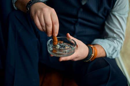 Man puts out a cigar in an ashtray, closeup view