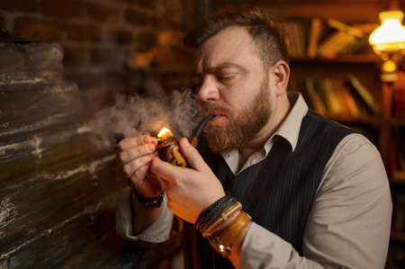 Bearded man lights smoking pipe with a match Imagens