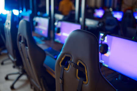 Row of monitors with headsets, gaming club, nobody