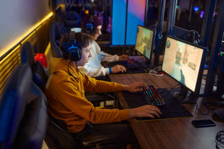 Two young gamers in headsets play in video game club