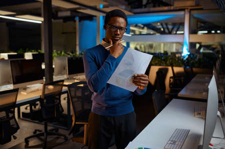 Man in glasses looks at charts, office lifestyle