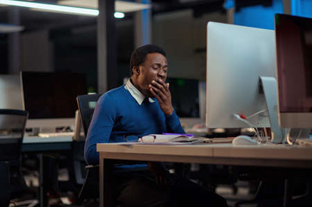 Tired young man works in night office