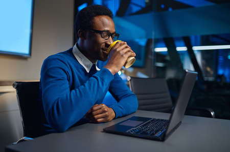 Manager in glasses works on laptop in night offic Imagens