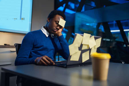 Stressed manager works on laptop, night office